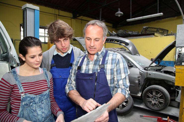 Ein Mann mit weißen Haaren in Arbeitshose erklärt zwei Auszubildenden (Mädchen und Junge) etwas auf einem Papier. Sie stehen in einer Autowerkstatt