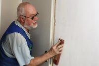 Mann mit grauen Haaren und Bart schleift eine verputzte Wand mit Schmirgelpapier ab