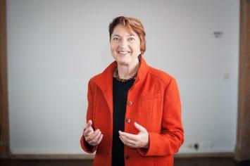 Bild von lachender Annelie Buntenbach in roter Jacke vor weißer Wand