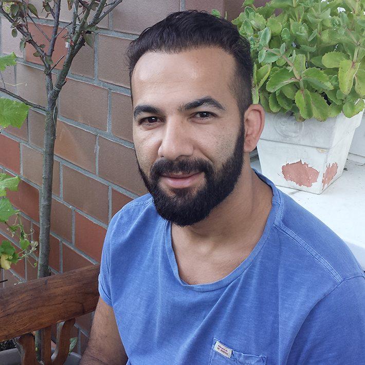 Porträt von Mann mit Bart und dunklen Haaren, der auf einer Bank sitzt