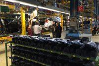 Fotograf fotografiert Arbeiter in Montagehalle und wird dabei selbst fotografiert