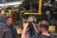Filmteam aus Interviewer und Kameramann steht vor Arbeiter in einer Montagehalle, sie lächeln