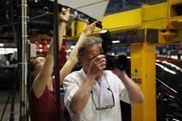 Fotograf in Montagehalle, hinter ihm hält eine Frau ein Lichtsegel hoch