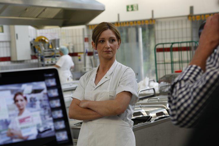 Frau in weißer Arbeitskleidung steht in der Großküche, am Bildrand ist Fotograf zu sehen, in dessen Kamera sie schaut