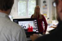 Frau steht im Büro; im Vordergrund am Bildrand zwei Männer, einer hält ein Tablet mit Film von Frau im Büro
