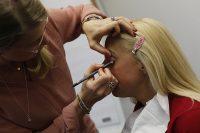 Frau wird von einer Stylistin geschminkt