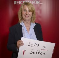 """Frau hält Schild mit Text """"Sekt und Selters"""""""
