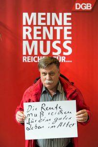 """Mann hält Schild mit Text """"Die Rente muss reichen für ein gutes Leben im Alter"""""""