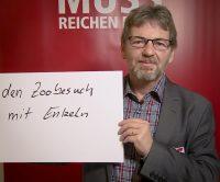 """Mann hält Schild mit Text """"den Zoobesuch mit Enkeln"""""""