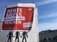 """Blow-up Poster mit Kampagnenmotiv mit rotem Banner """"Rente muss für ein gutes Leben reichen"""" Kurswechsel: Die gesetzliche Rente stärken"""" wird aufgehängt"""