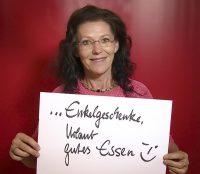 """Frau hält Schild hoch mit Text: """"Enkelgeschenke, Urlaub, gutes Essen, """"Zwinkersmiley"""""""