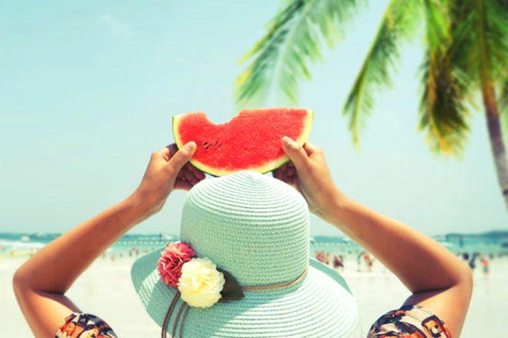 Urlauberin mit Sonnenhut am Palmenstrand hält Melone
