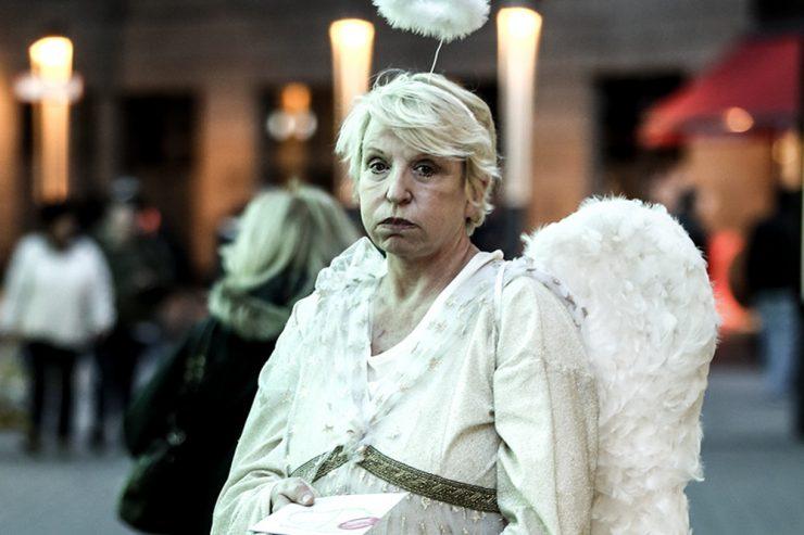 Ältere Frau in Weihnachtsengel-Kostüm verteilt lustlos Flyer in Fußgängerzone