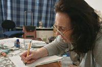 Ältere Frau sitzt an Couchtisch und geht Rechnungen durch