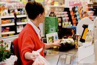 Kassieren im Supermarkt zieht Lebensmittel über den Scanner der Kasse