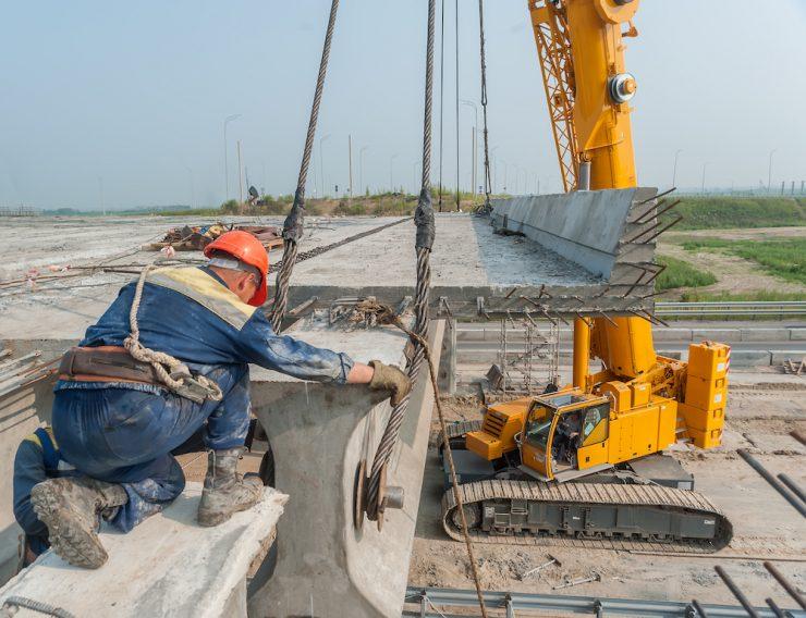 Arbeiter beim Brückenbau, der ein Betonbauteil, das von einem Kran herabgelassen wird annimmt und austariert.
