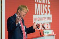 """Redner bei der DGB Rententagung steht am Pult, im Hintergrund rote Rückwand mit dem Titel der Kampagne """"Rente muss für ein gutes Leben reichen""""."""