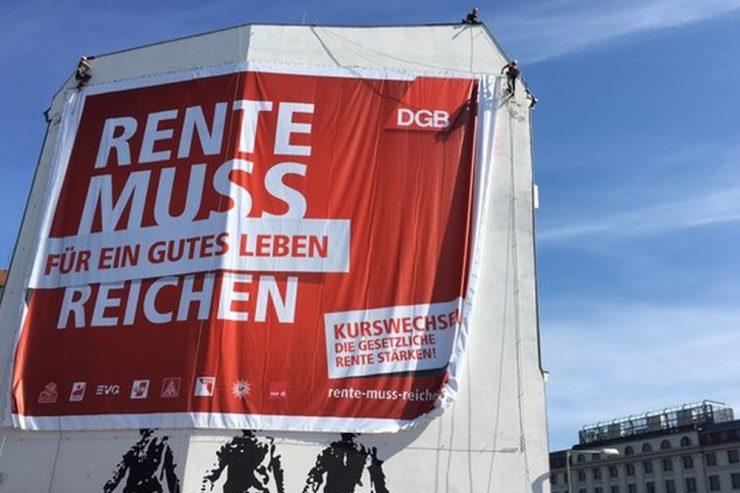 """Groß-Plakat mit der Aufschrift """"Rente muss für ein Gutes Leben reichen"""" an einer Hausfassade"""