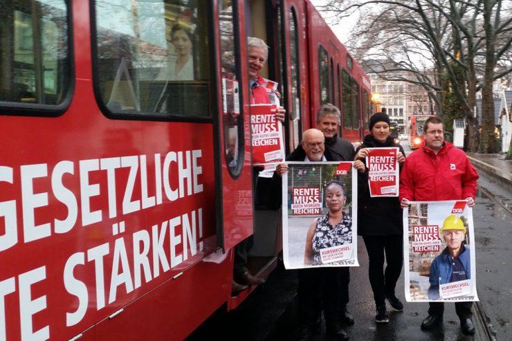 Menschen mit Plakaten zur DGB-Rentenkampagne vor einer Straßenbahn mit dem Slogan der DGB-Rentenkampagne