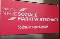"""Pinkes Schild mit der Aufschrift """"Initiative Neue Soziale Marktwirtschaft - Spalten ist unser Geschäft"""""""