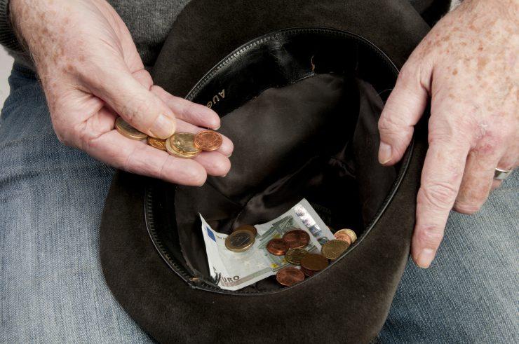 Hände eines älteren Mannes halten einen Hut, in dem ein 5-Euro-Geldschein und wenige Münzen liegen.