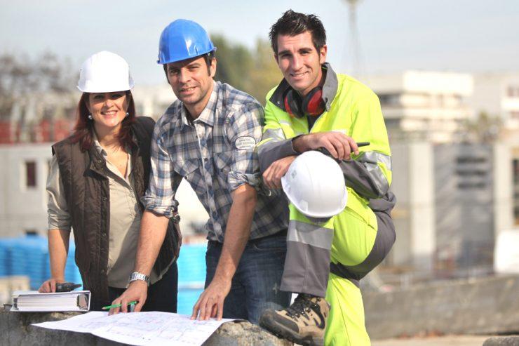 Zwei Männer und eine Frau mit Bauhelmen vor einem Bauplan auf einer Baustelle