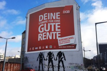Ein Riesenbanner des DGB auf einer Hauswand. Es trägt die Aufschrift: Deine Stimme für eine gute Rente. Kurswechsel: Die gesetzliche Rente stärken!