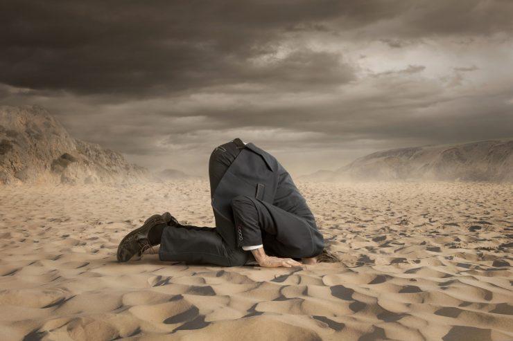Mann in Anzug steckt seinen Kopf in den Sand. Am Himmel ziehen Gewitterwolken auf.