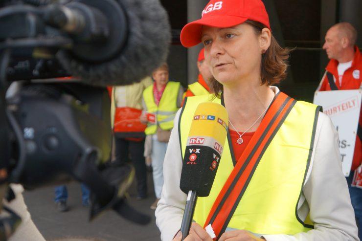 Frau mit DGB-Mütze gibt einem Kamerateam ein Interview
