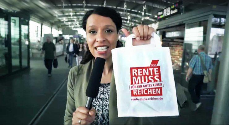 """Reporterin hält Tüte mit Logo """"Rente muss für ein gutes Leben reichen"""" in die Kamera"""
