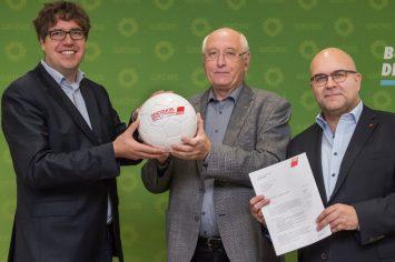 Drei Männer halten einen Fußball