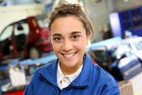 Junge Mechanikerin in Autowerkstatt