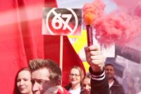 """Hand mit """"Pyrorauch""""-Stange, im Hintergrund Demonstranten einer Demo und ein Schild mit einer durchgestrichenen """"67"""" (Gegen die Rente mit 67)"""